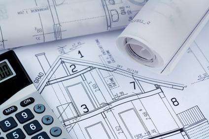 Ein Bauplan eines Architekten mit einem Taschenrechner. Symbolfoto für Finanzierung und Planung eines neuen Hauses.